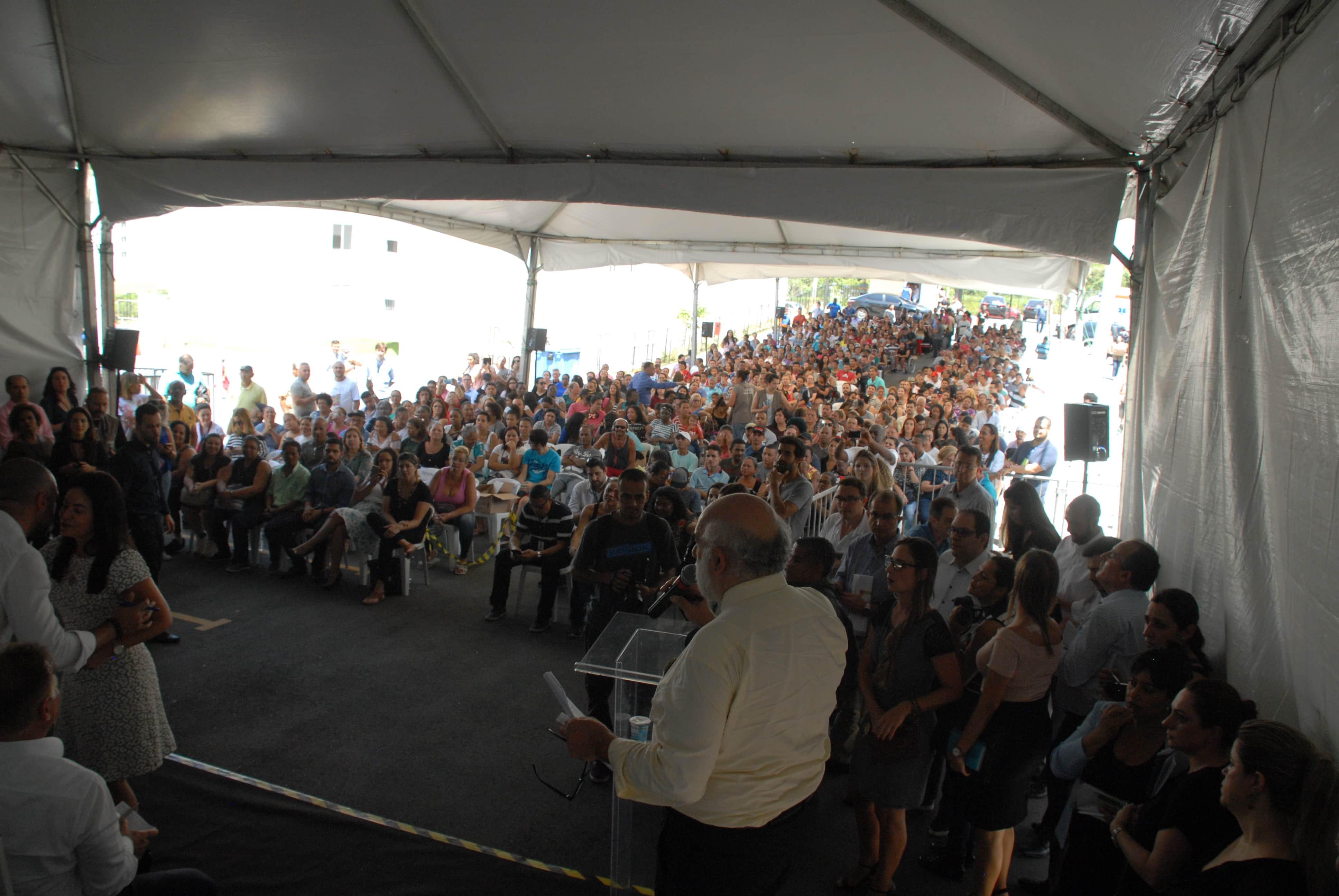 Foto aberta, vinda vinda do palco, mostrando as costas das pessoas em pé do palco, falando com uma multidão de pessoas sentadas em baixo de uma lona