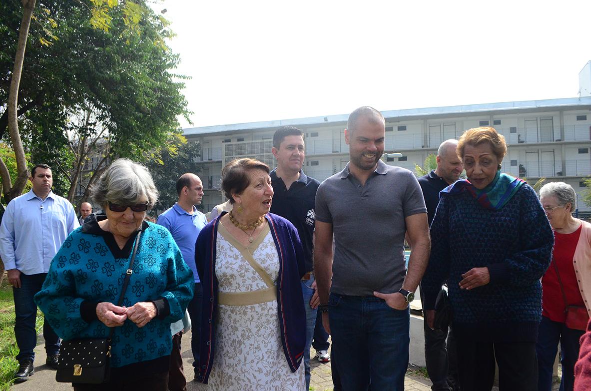 Na foto está o prefeito Bruno Covas andando juntamente com as idosas da Vila.