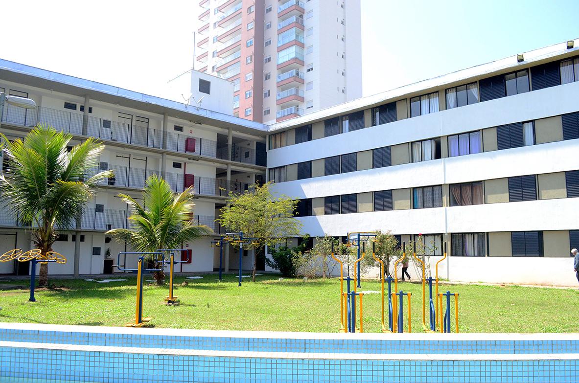 A foto foi tirada ao longe pegando toda a fachada de frente da Vila dos Idosos, inclusive equipamentos de academia que há na praça.
