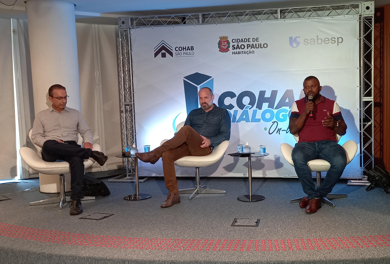 """Os três convidados do Cohab Diálogos sentados. Ao fundo um grande backdrop escrito """"Cohab Diálogos"""""""