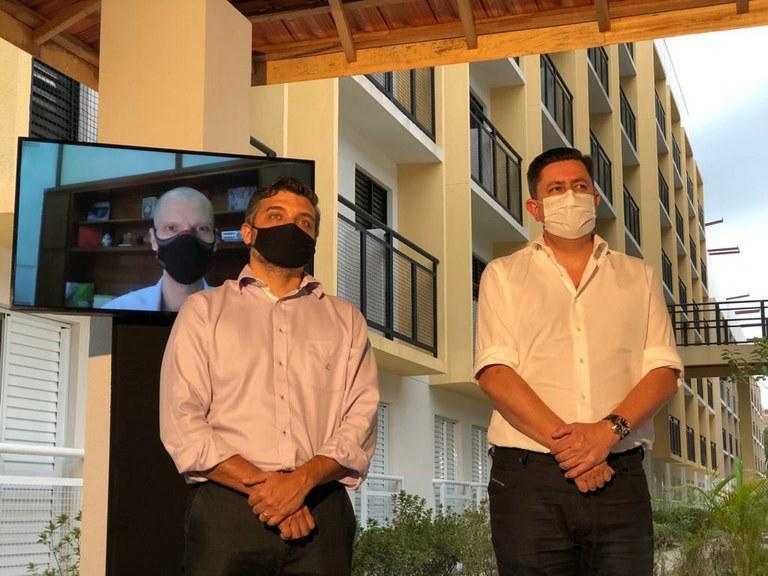 A imagem mostra o presidente da Cohab São Paulo, Alex Peixe, ao lado direito da imagem. Junto dele está o secretário municipal de habitação Orlando Faria. Em uma tela de televisão está o prefeito Bruno Covas, que acompanha a entrega de modo virtual.