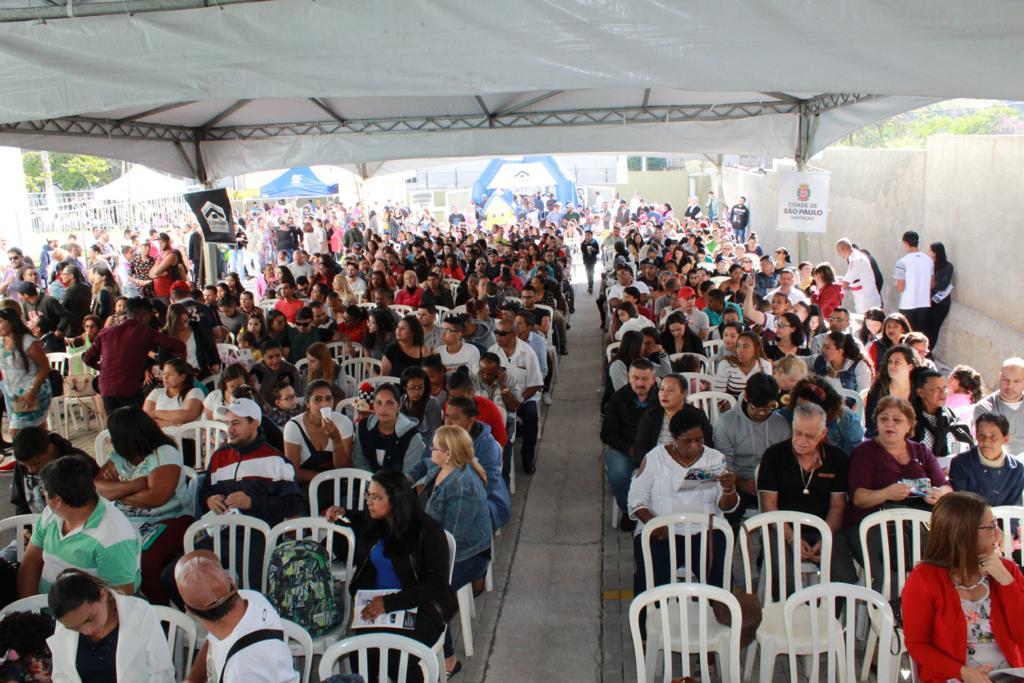 A foto foi tirada do alto, do evento. Na imagem estão os mutuários sentados esperando para o discurso.