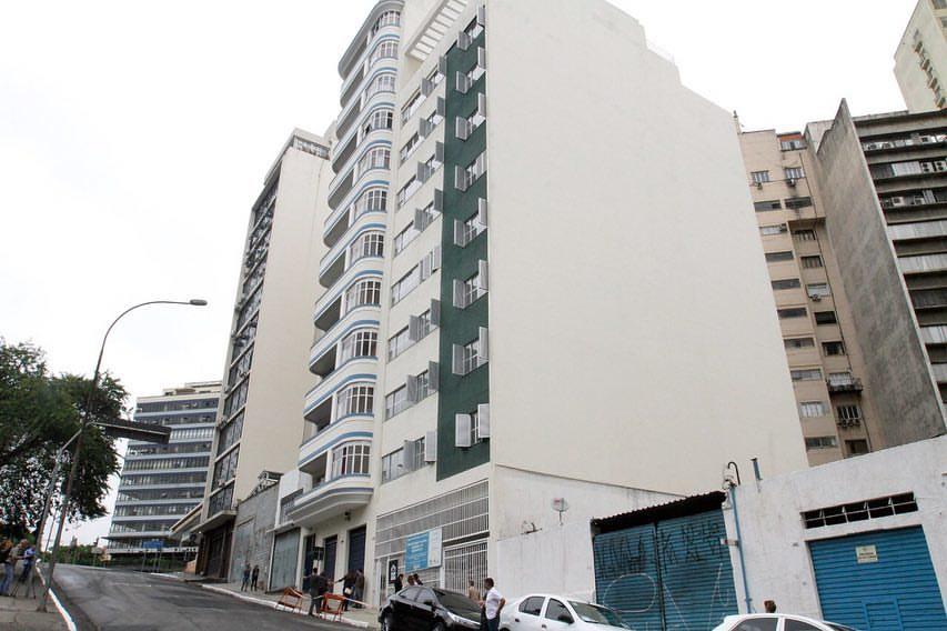 Imagem da rua com a faxada do prédio que possui as cores creme e verde