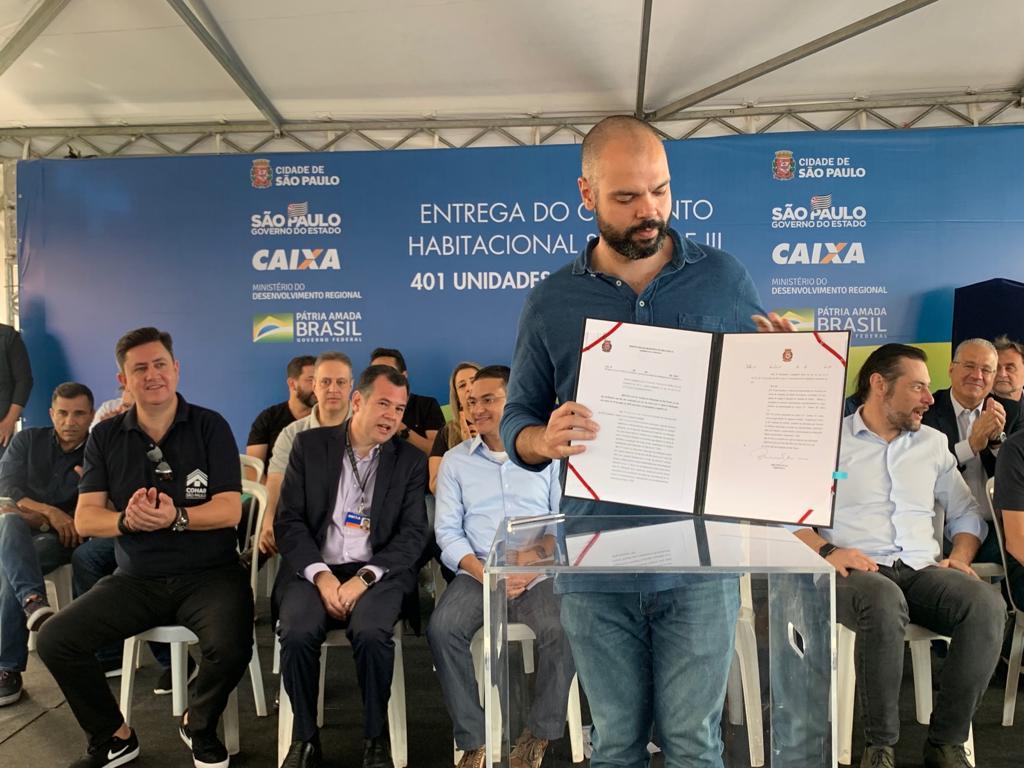 Na imagem está o Prefeito de São Paulo Bruno Covas segurando o ermo assinado para entregar as 401 unidades habitacionais.