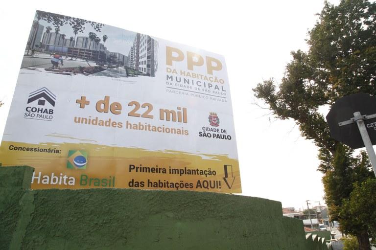 """Cartaz com os dizeres """"PPP da Habitação Municipal da cidade de São Paulo"""" em preto na parte superior direita da placa. Abaixo centralizado está escrito em laranja. """"Mais de 22 mil unidades habitacionais""""."""