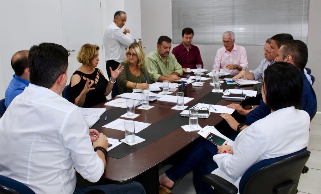 A foto foi tirada da diagonal da mesa, mostrando a reunião inteira. Com todos os diretores dos setores, com papeis e copos d'água em cima da mesa.