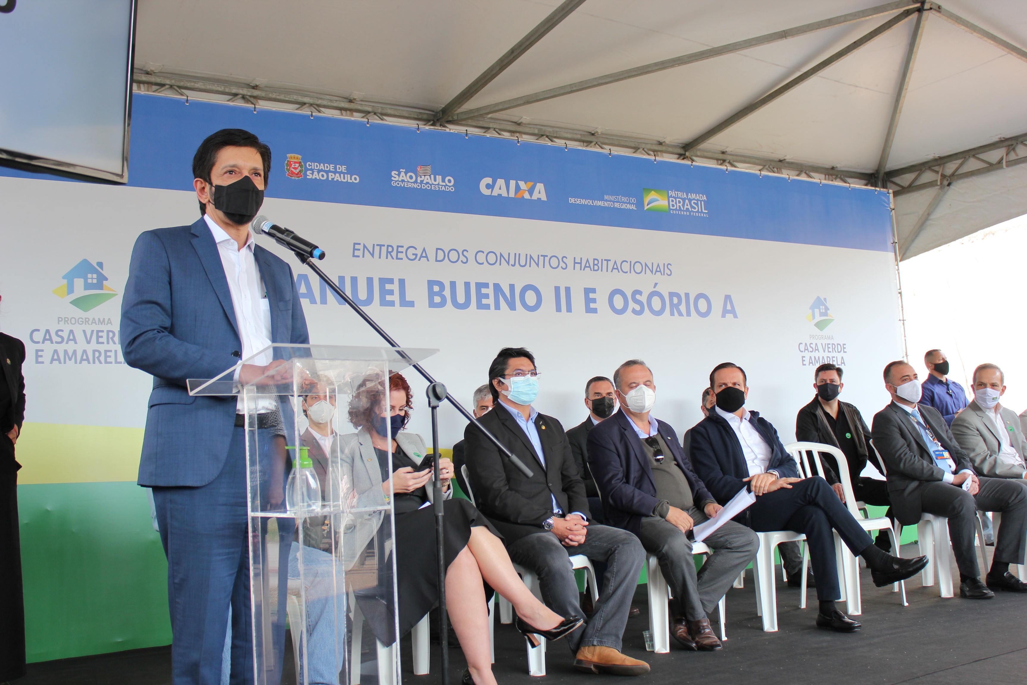 Na imagem, o prefeito Ricardo Nunes está fazendo um discurso no púlpito na parte esquerda da foto. Ele está acompanhado de autoridades que estão sentadas em cadeiras. Todos estão usando máscara.