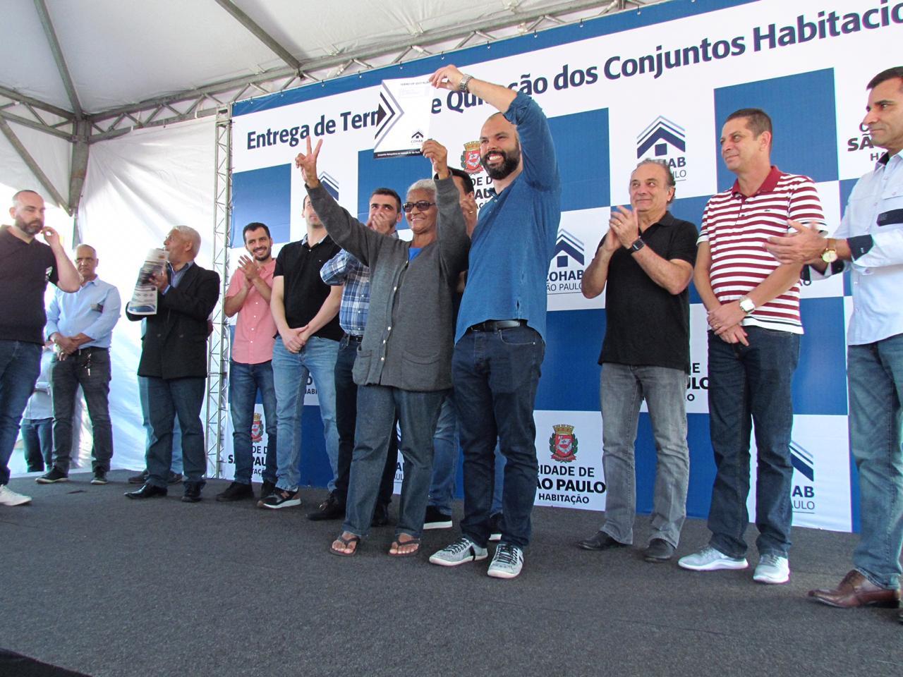 A foto está mostrando o prefeito de São Paulo Bruno Covas e uma mutuária segurando o termo de quitação e sorrindo. Ao lado deles estão vários trabalhadores do setor público aplaudindo.