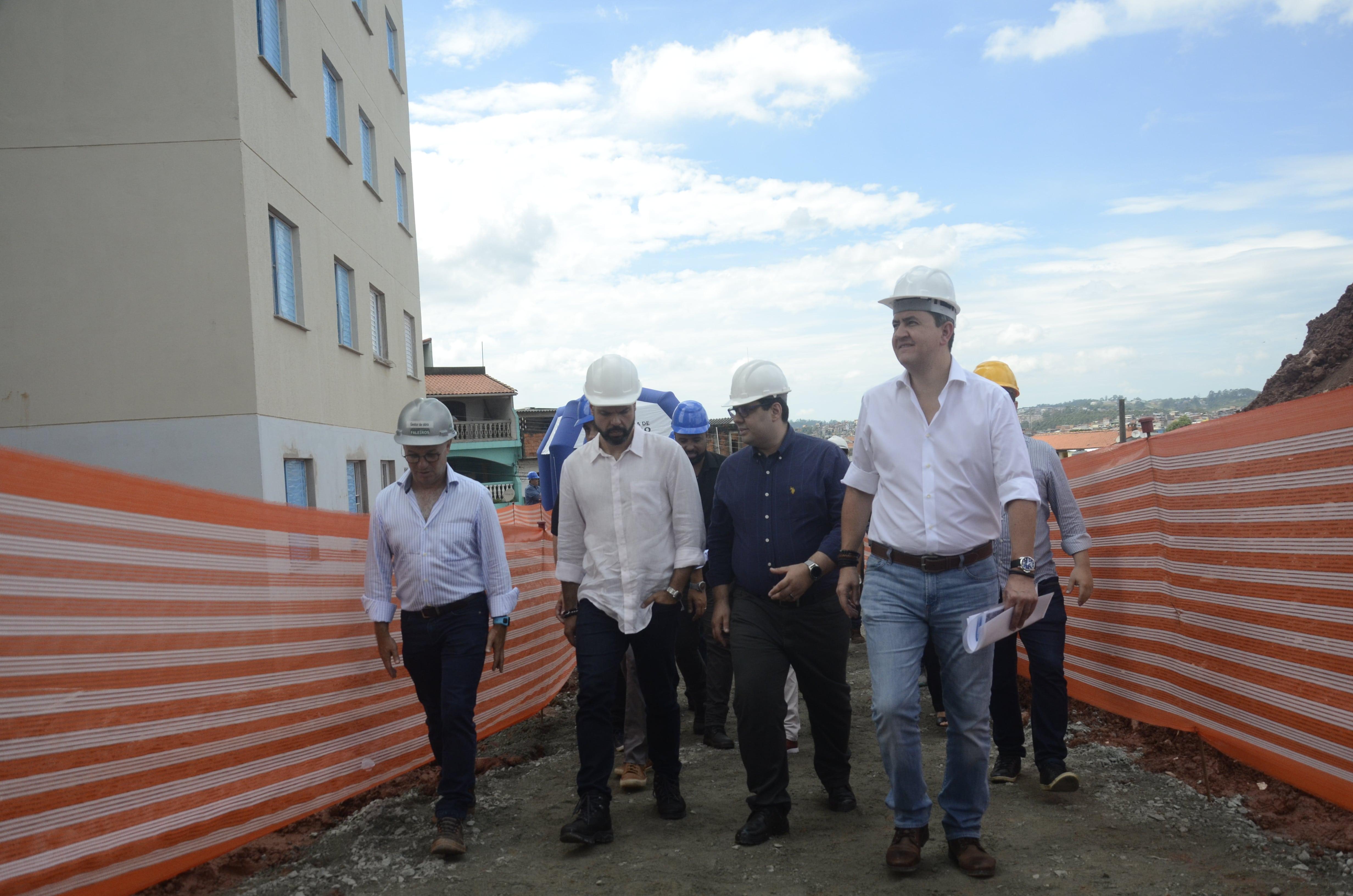 O Prefeito de São Paulo Bruno Covas e Presidente da Cohab Alexsandro Peixe caminhando em meio a duas divisórias sinalizando o local das obras