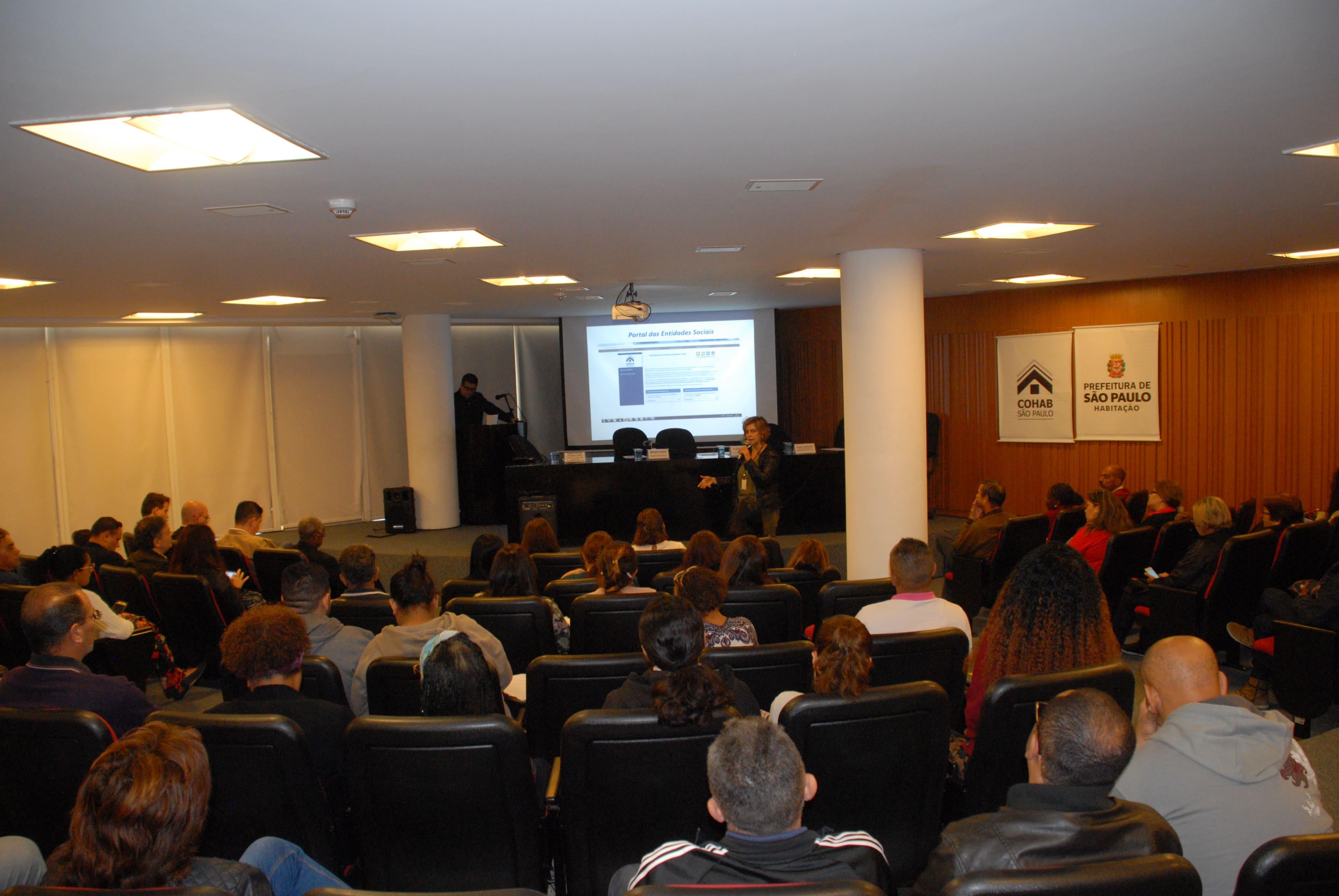 Diretora Administrativa da Coha, Renata Soares no fundo realizando sua palestra para o público sentado no primeiro plano