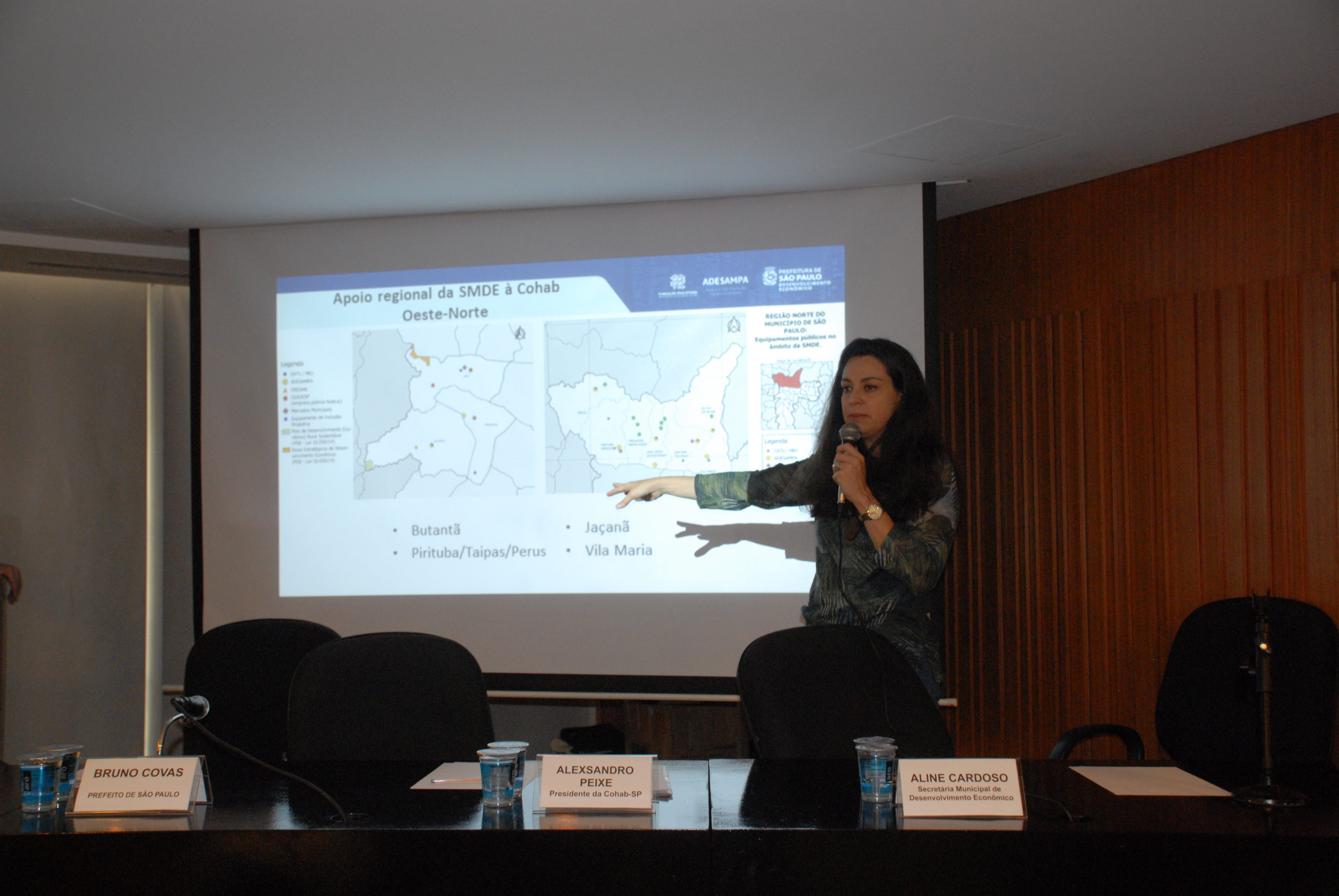 Foto com a Secretária Municipal de Habitação Aline Cardoso realizando sua apresentação apontando para um mapa na tela de projeção