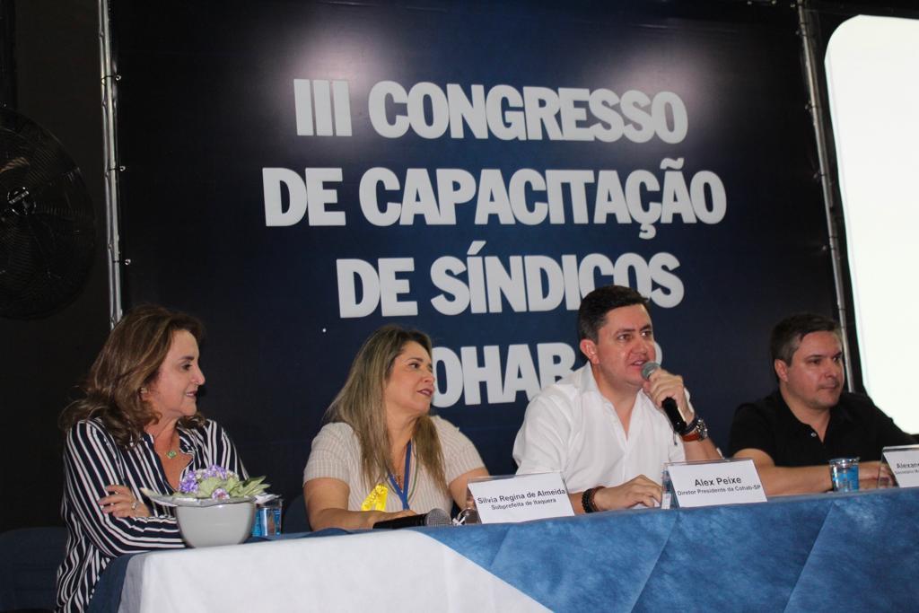 A foto foi tirada no Congresso dos Síndicos, com o presidente da Cohab Alex Peixe presente e com o microfone na boca, acompanhado pela subprefeita de Itaquera e mais alguns representantes do bairro.