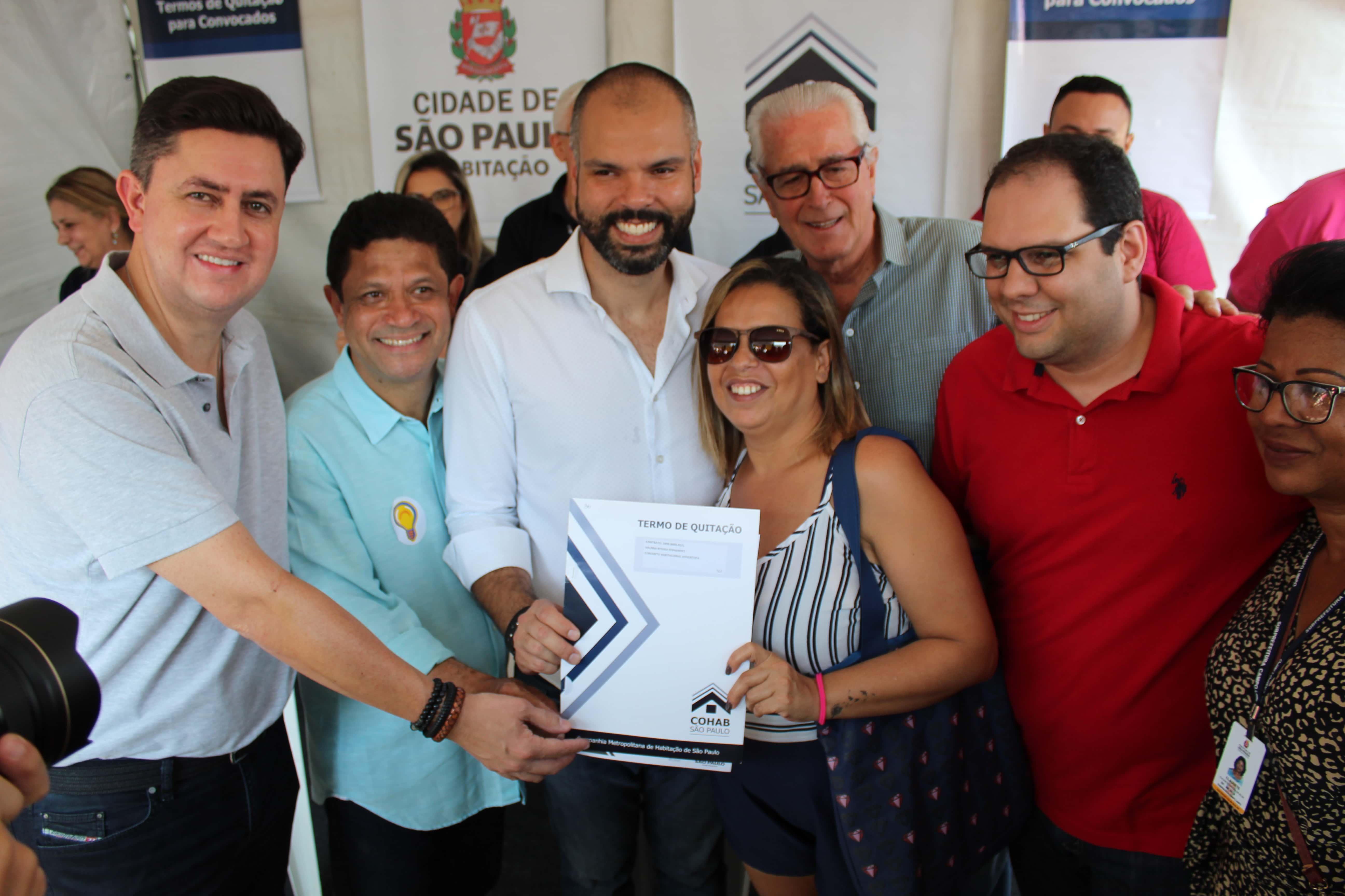 Na imagem está o prefeito de São Paulo Bruno Covas, o presidente da Cohab-SP Alexandro Peixe, e o secretário municipal de habitação Aloisio Pinheiro segurando o termo  de quitação entregue para mutuária.