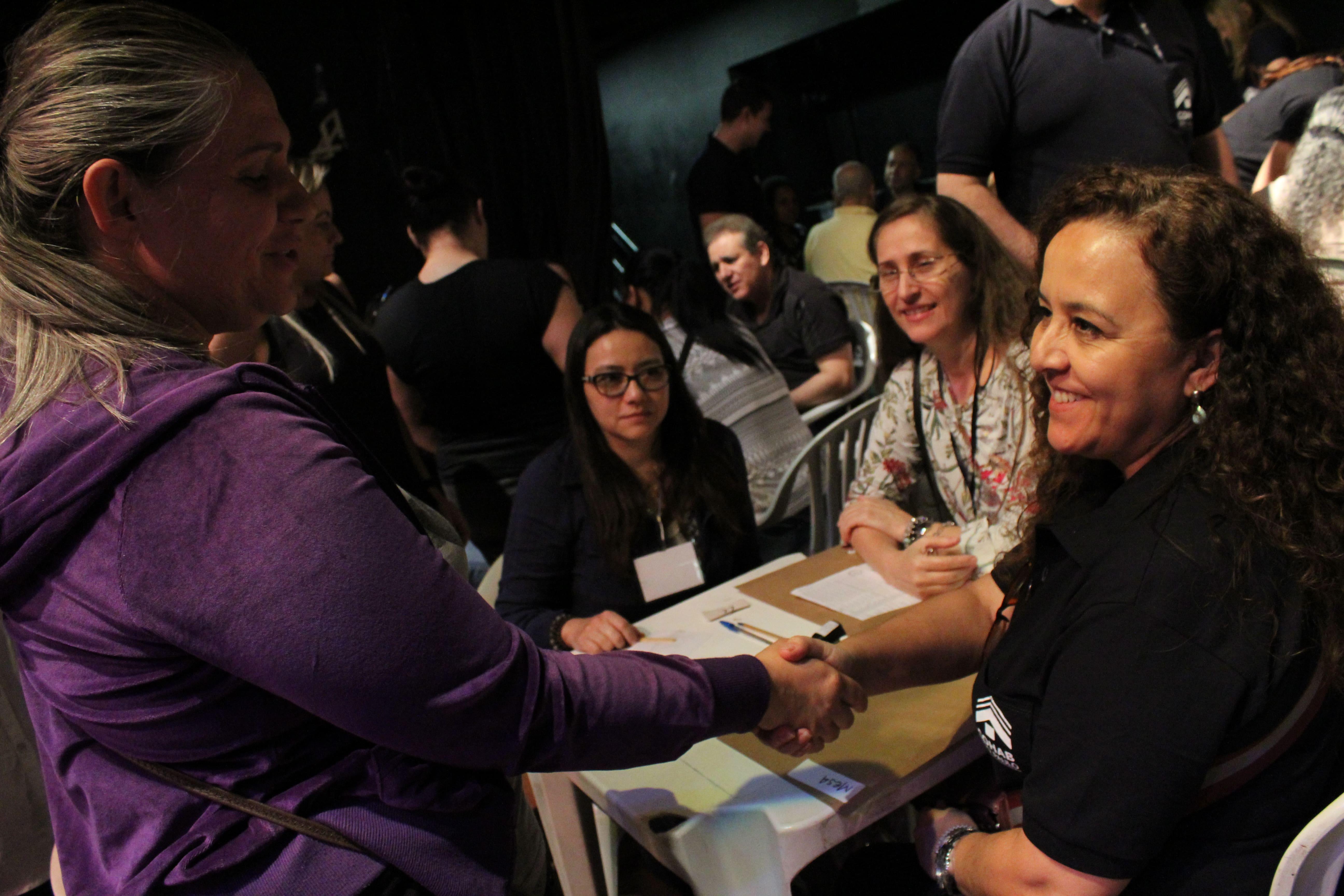 Imagem da hora do aperto de mão entre mutuário, a esquerda da foto, e da funcionária da Cohab, a direita, após ser firmado o acordo de renegociação