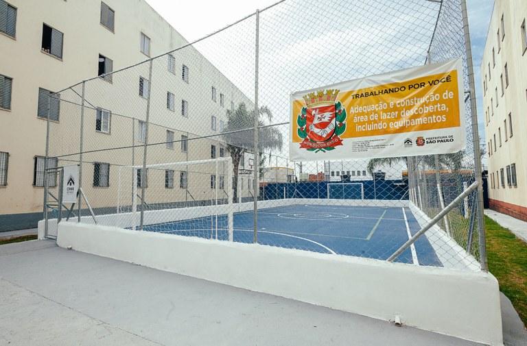 Foto da quadra poliesportiva, ao fundo o prédio do Conjunto Habitacional Minas Gás
