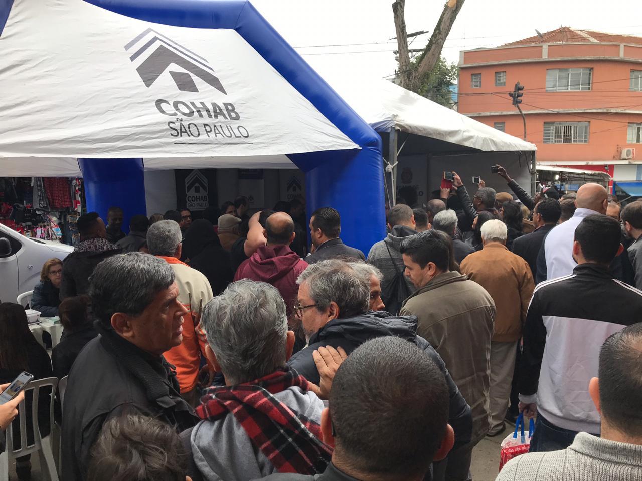 A foto foi tirada de longe e mostra a tenda da Cohab com os mutuários.
