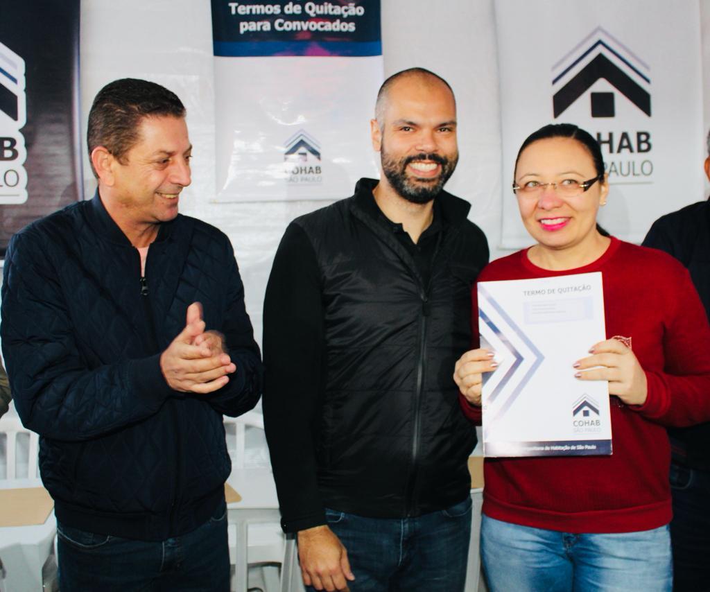 Na foto, estão todos sorrindo para a câmera. O prefeito da cidade de São Paulo Bruno Covas está ao lado da mutuária com o termo de quitação em mãos.
