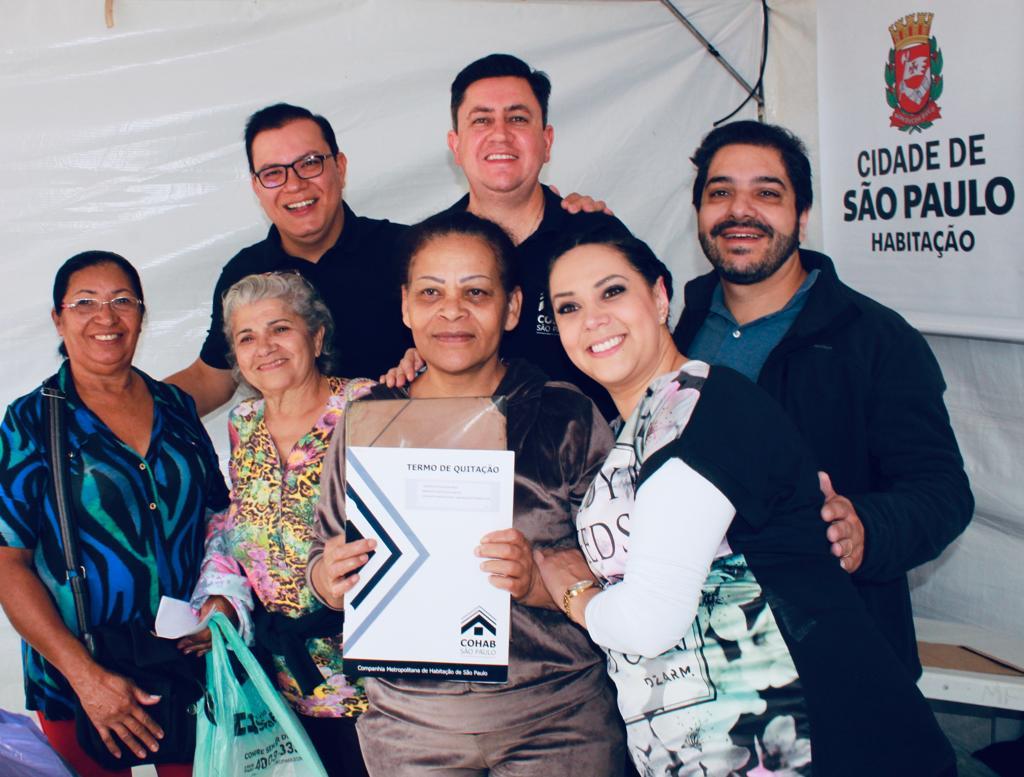 Na imagem está o presidente da Cohab Alexsandro Peixe segurando o termo de quitação juntamente com vários mutuários. Todos sorrindo para a câmera.