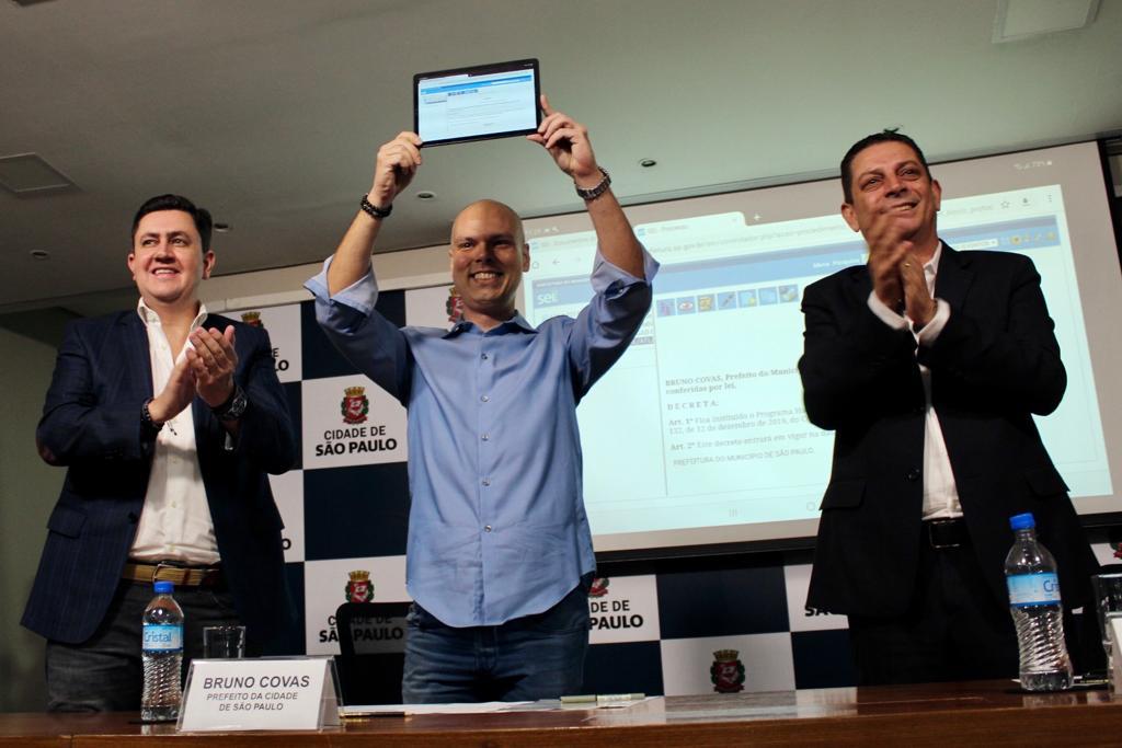 Prefeito de São Paulo, Bruno Covas, ao centro, segurando o dispositivo eletronico que utilizou para assinar oficialmente o novo programa habitacional. Ao lado esquerdo da foto se encontra o Presidente da Cohab-SP Alex Peixe e do lado direito o Secretário Municipal de Habitação, João Farias