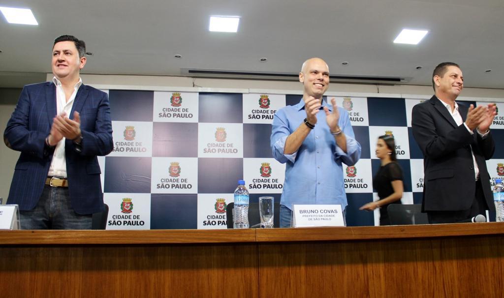 Prefeito Bruno Covas, Presidente da Cohab Alex Peixe e Secretário João Farias estão de pé batendo palmas