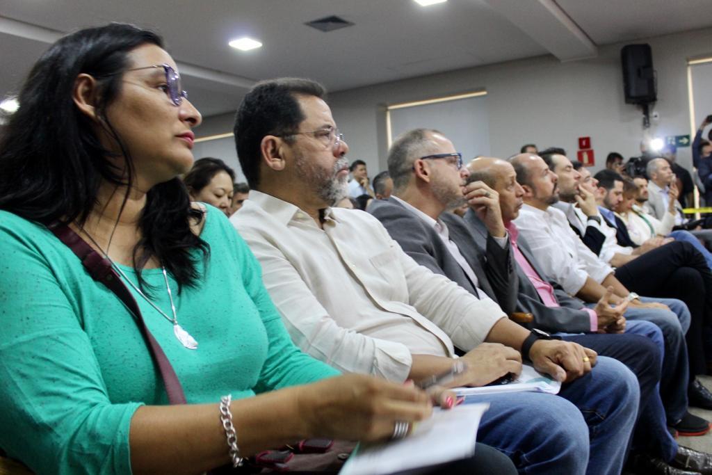 Pessoas assistindo atentamente a cerimônia para início do Programa