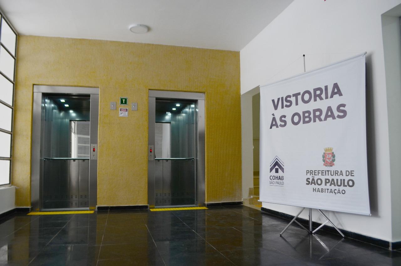 """Imagem com dois elevadores ao centro. Do lado direito da foto uma placa escrita """"vistoria a obra"""""""
