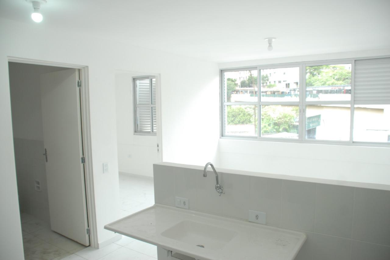Imagem da parte de dentro do apartamento. Na direita uma cozinha americana, na esquerda a porta de entrada do banheiro e do quarto