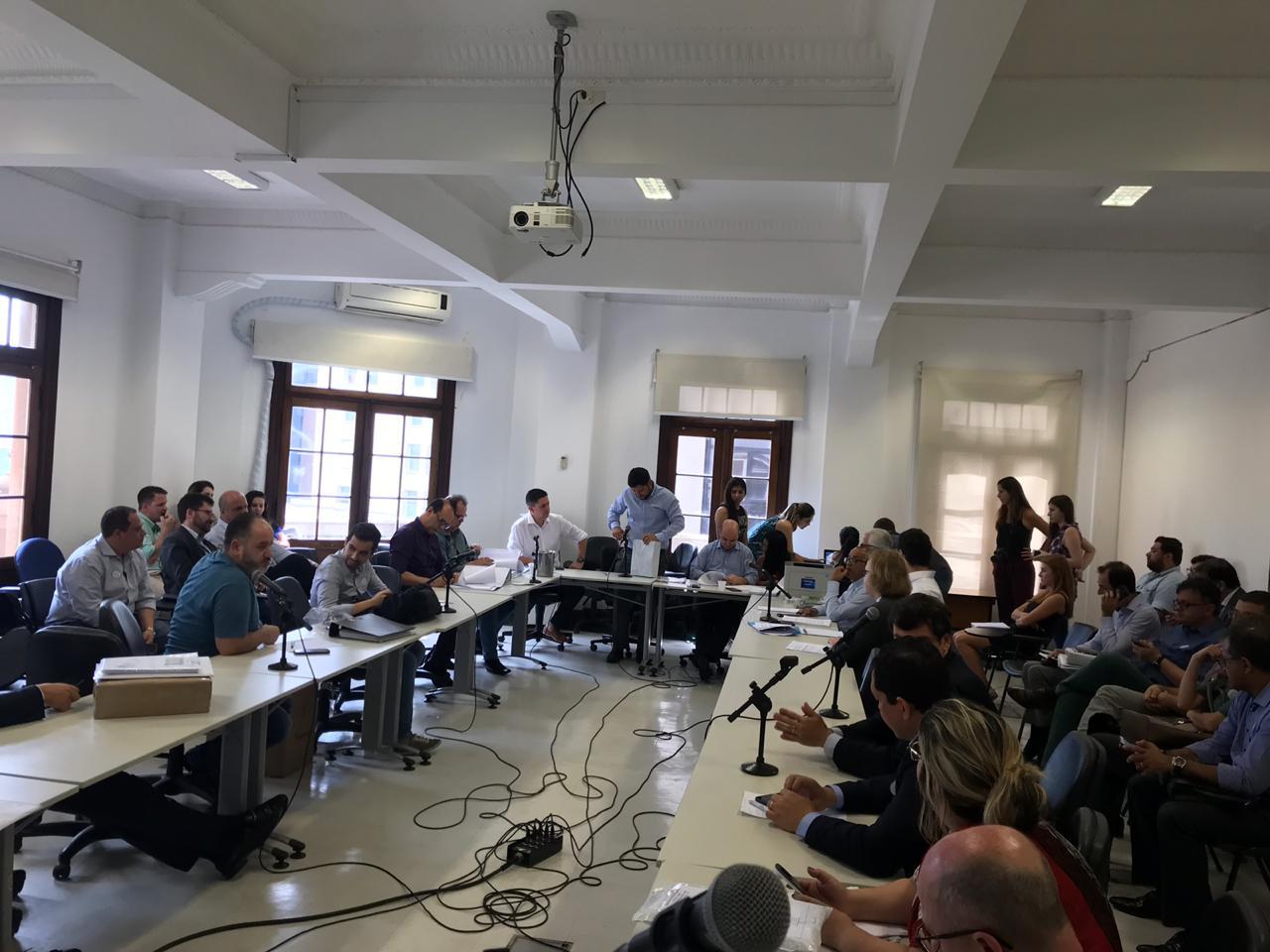 Foto em sala com mesa em U. Pessoas assistem ao presidente da Cohab Alexsandro Peixe abrindo os envelopes das empresas