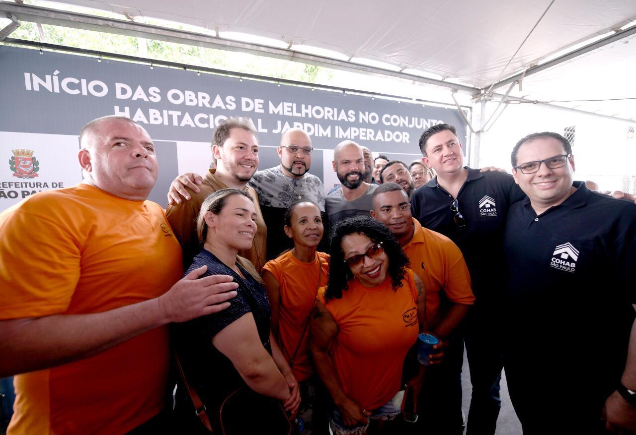 Autoridades e equipe da prefeitura vestido camisetas laranjas, posam para foto na cerimônia de início das obras.