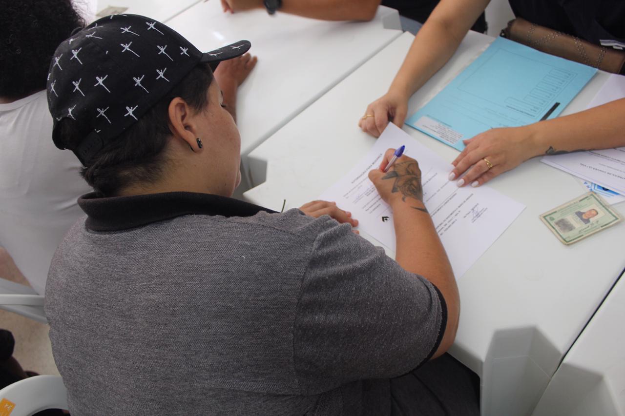 Moradora de camisa cinza e boné, assinando seu o contrato de locação social que permitirá que ela resida no empreendimento.