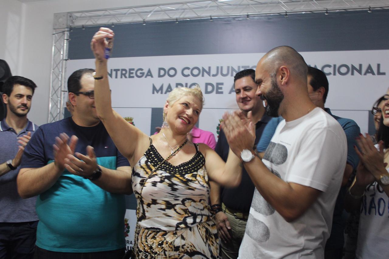 mulher com vestido amarelo e preto levanta alto a chave do seu apartamento, olhando com felicidade para o Prefeito Bruno Covas que está a sua esquerda.