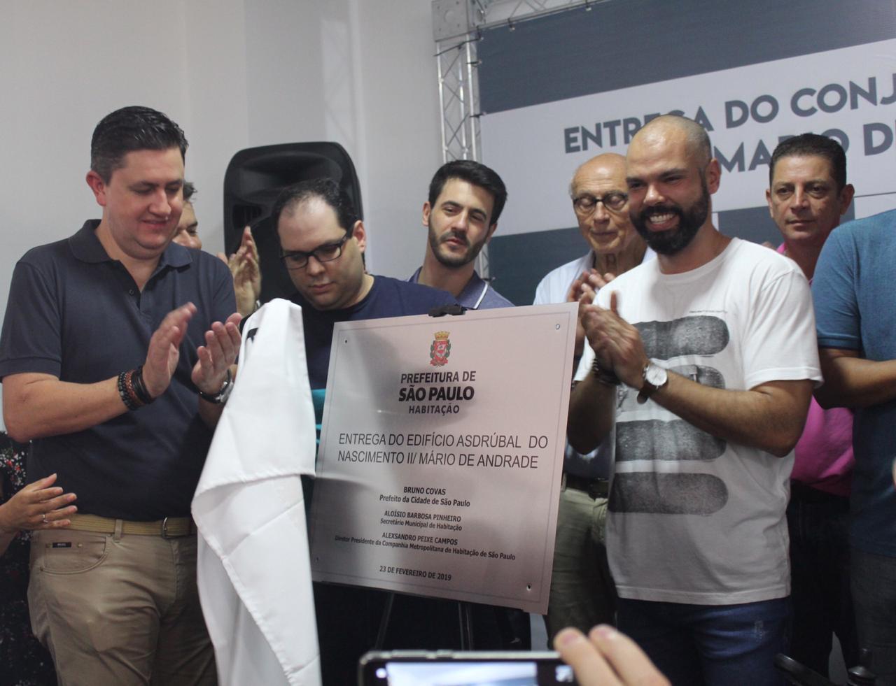 """Prefeito de Bruno Covas junto com o Presidente da Cohab Alexsandro Peixe revelam a placa de inauguração do empreendimento. A placa está escrito """"E ntrega do edifício Mário de Andrade/ Asdrúbal do Nascimento II."""