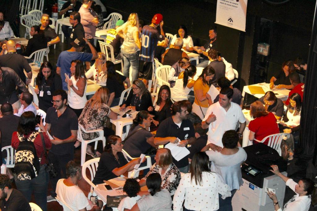 A foto foi tirada de cima, mostrando uma parte do auditório com os mutuários sendo atendidos pelos colaboradores.
