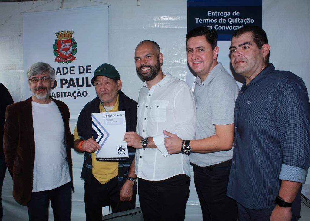 Na foto, da direita para a esquerda está o deputado federal, seguido do presidente da Cohab Alexsandro Peixe e ao lado o prefeito Bruno Covas juntamente com o senhor Delmiro segurando o termo de quitação.