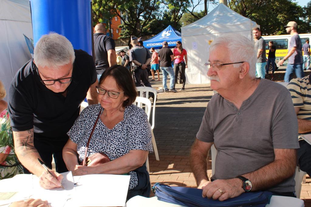 Na imagem, estão três mutuários sentados olhando para a mesa que está o termo de quitação e o mutuário situado a esquerda da foto está assinando o contrato.