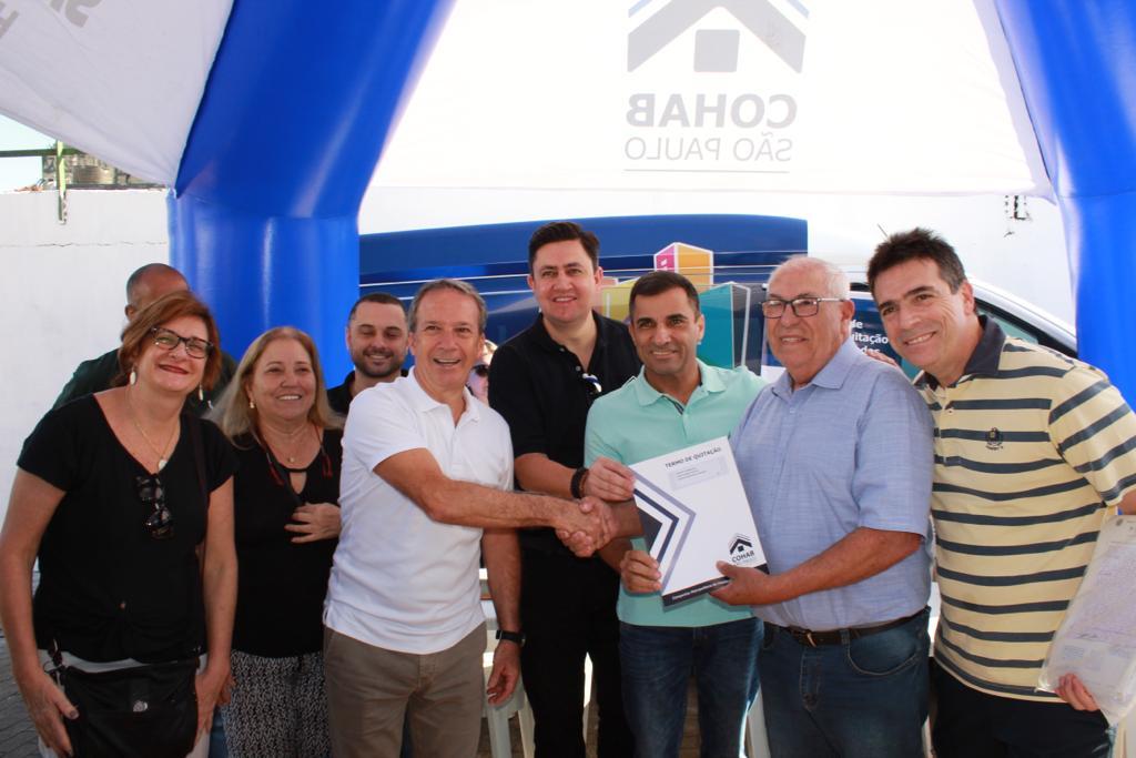 Na imagem, está o presidente da Cohab Alexsandro Peixe segurando o termo de quitação, com mutuários e representantes da habitação.