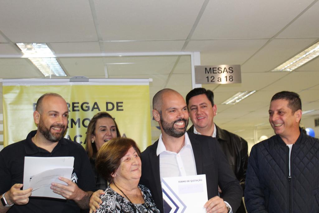 Na imagem, mostram alguns representantes da Cohab juntamente com o presidente da Companhia Alexsandro Peixe, o prefeito da cidade de São Paulo Bruno Covas e uma mutuária com seu termo de quitação.