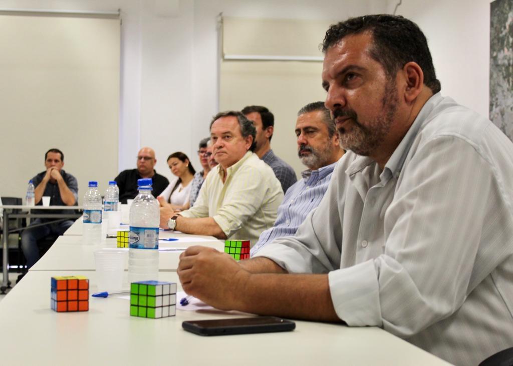 A foto foi tirada de diagonal, e mostra os colaboradores da Companhia, sentados, olhando para o presidente Alex Peixe. Na mesa estão garrafas d'água e o cubo mágico.