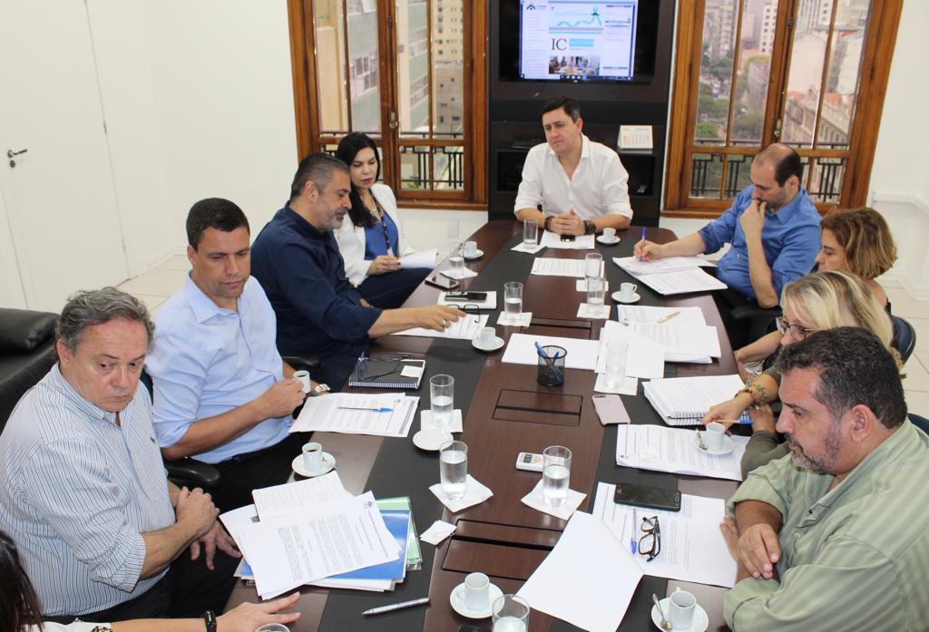 A foto foi tirada ao fundo da mesa de reunião, com o presidente da Cohab Alex Peixe, no topo da mesa. Aos lados estão todos os diretores dos setores da Companhia.