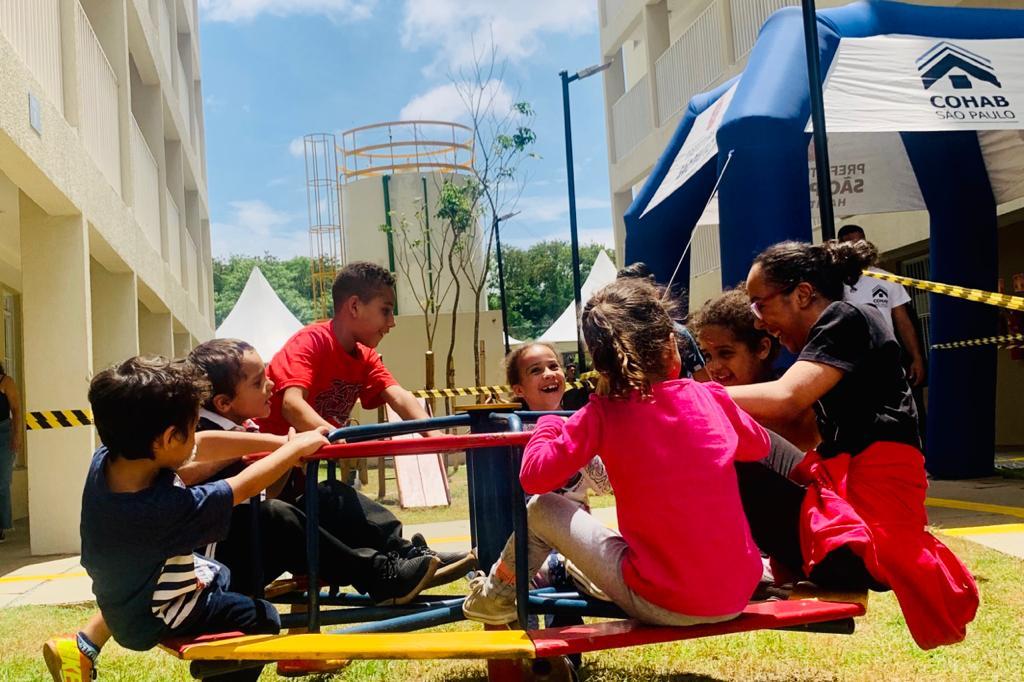 Crianças brincando no gira-gira do prédio. Ao fundo é possível ver a tenda da Cohab-SP
