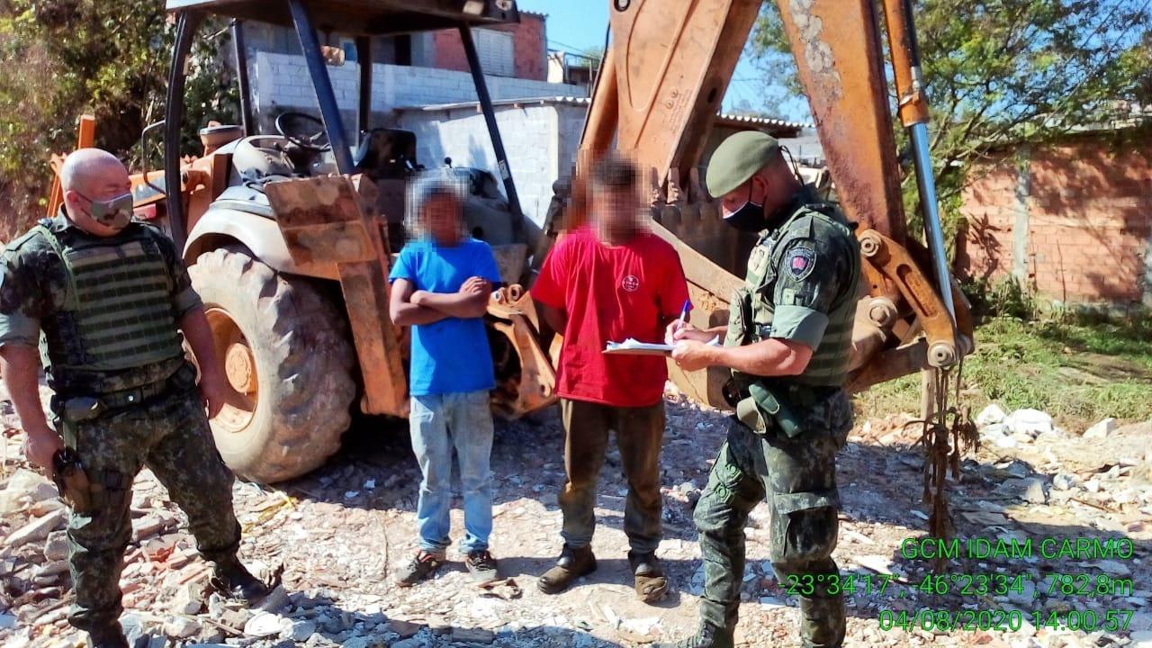 Imagem em área aberta. Dois policiais da GCM Ambiental, nas duas extremidades da foto, autuam os dois suspeitos, centralizados. Os homens detidos vestem uma camisa azul e vermelha. Ao fundo está o trator que eles usavam para praticar a ilegalidade. Os rostos dos suspeitos estão borrados.