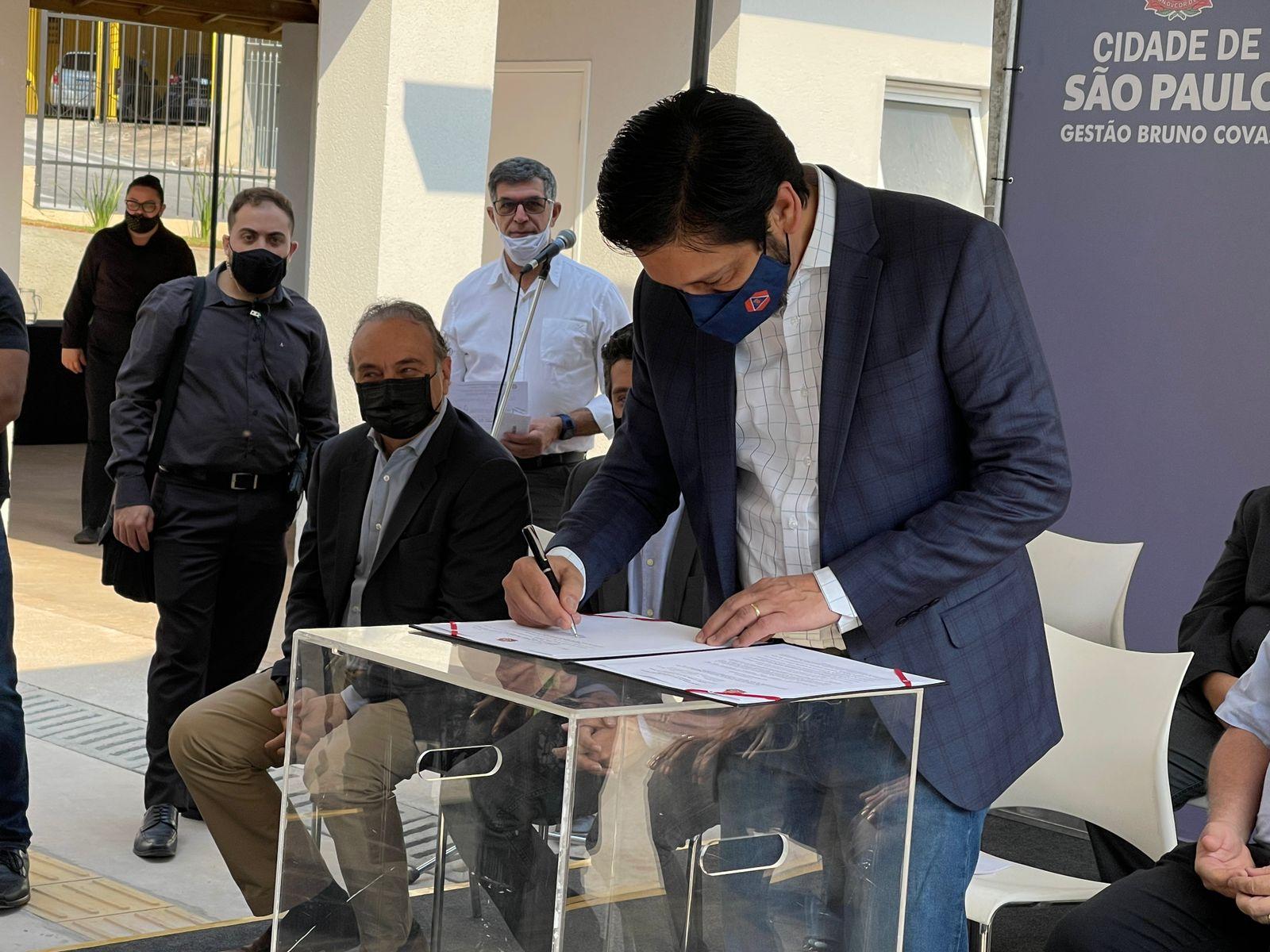 Fotografia do prefeito Ricardo Nunes, no palco, assinando o documento para a lei municipal de habitação do programa Pode Entrar. Pessoas ao fundo.
