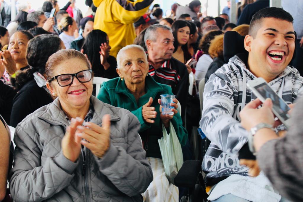 Na imagem estão os mutuários após a apresentação, sentados, batendo palmas.