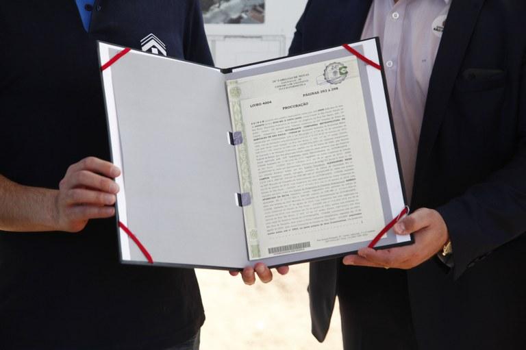 Foto com duas pessoas, mostrando apenas suas mãos. Elas estão segurando o termo de cessão do terreno para a concessionaria.