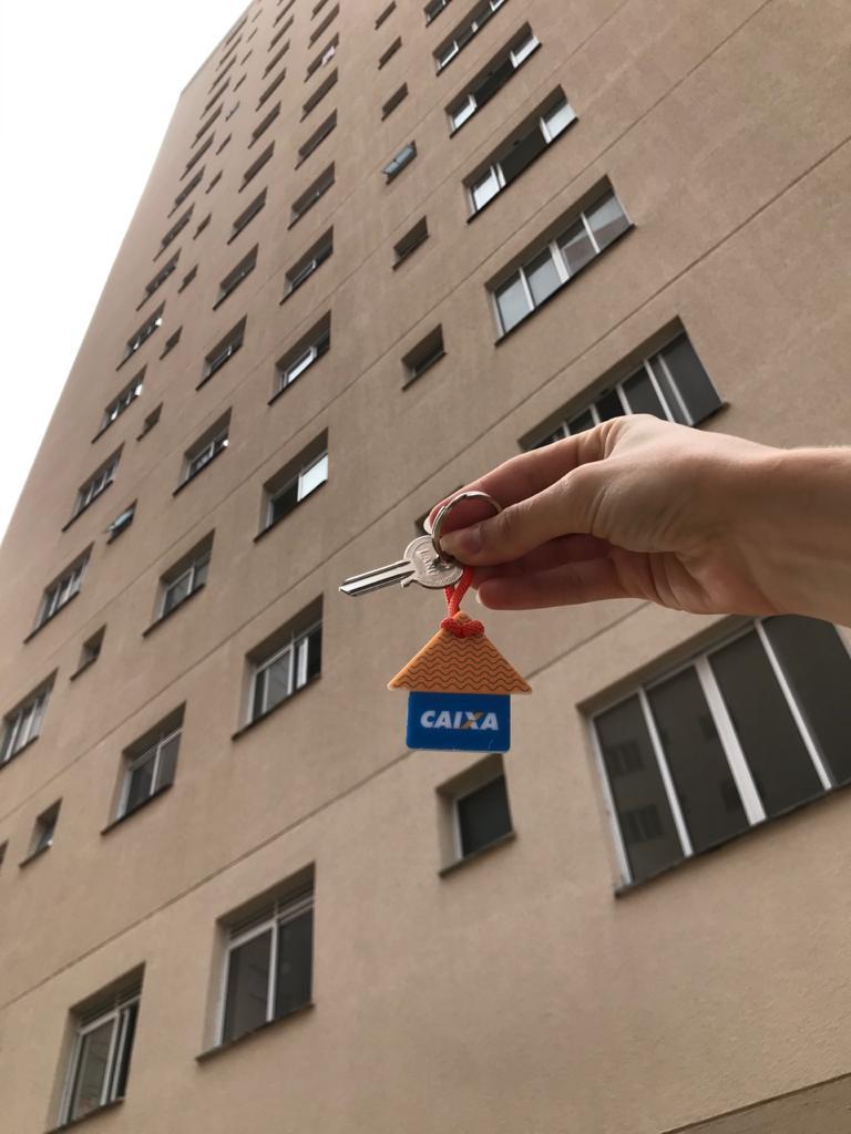 (Nas imagens: mascote Cohabinho segura a placa de inalguração, prédios ao fundo; mão segura uma chave, com chaveiro no formato de casa, de frente ao prédio inaugurado)