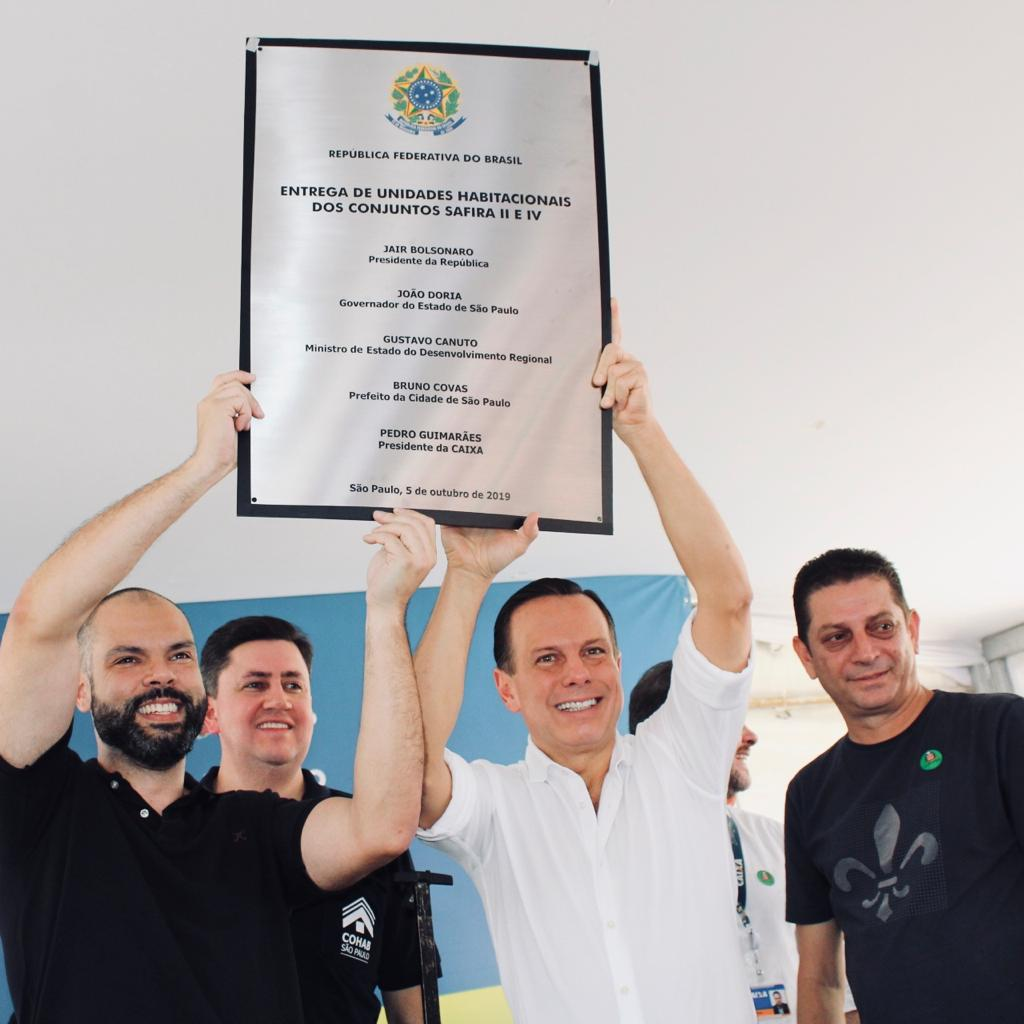 Da direita para a esquerda, está o prefeito da cidade de São Paulo, Bruno Covas, ao seu lado o presidente da Cohab Alex Peixe, ao lado dele o governador João Dória e por ultimo, o secretário de habitação João Farias.