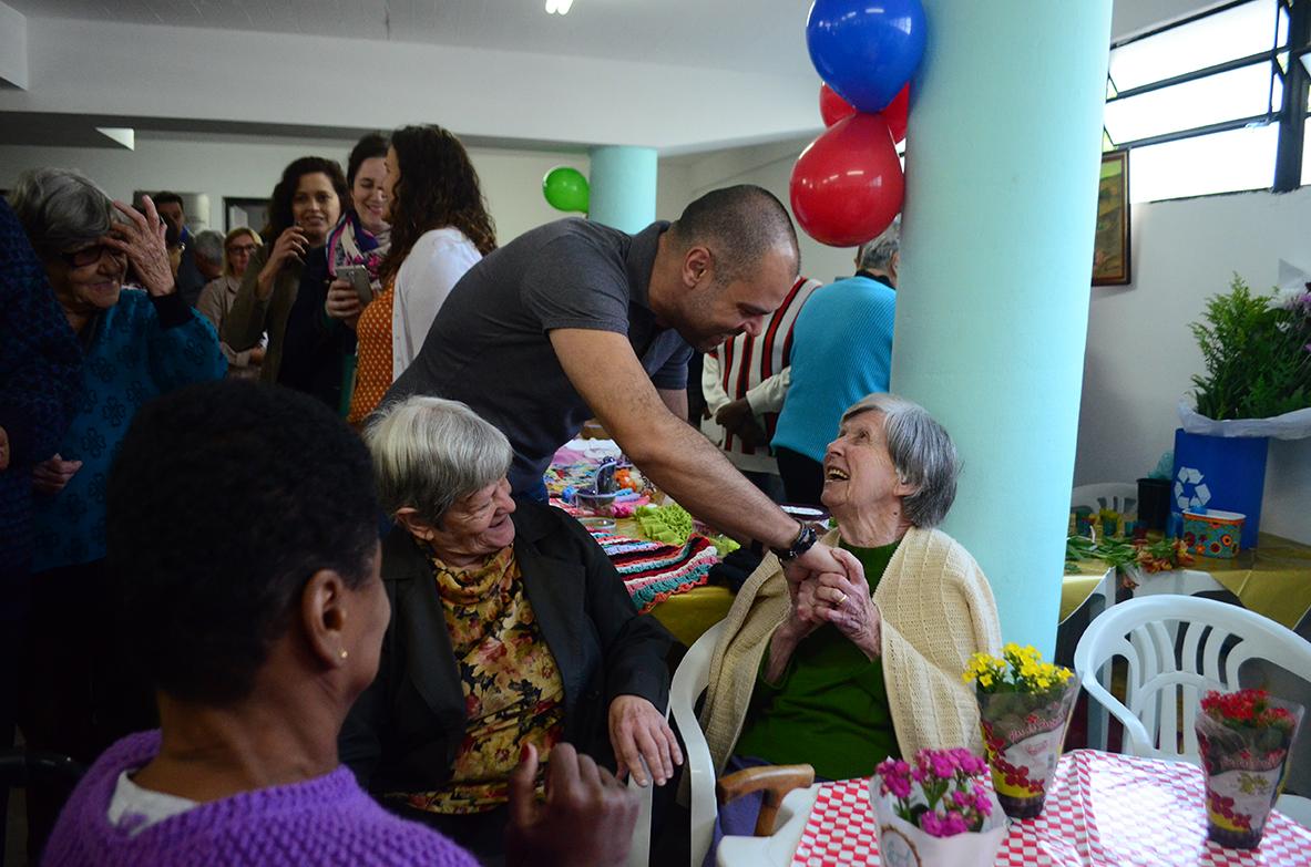 A foto mostra o Prefeito Bruno Covas cumprimentos idosas que estão sentadas conversando.