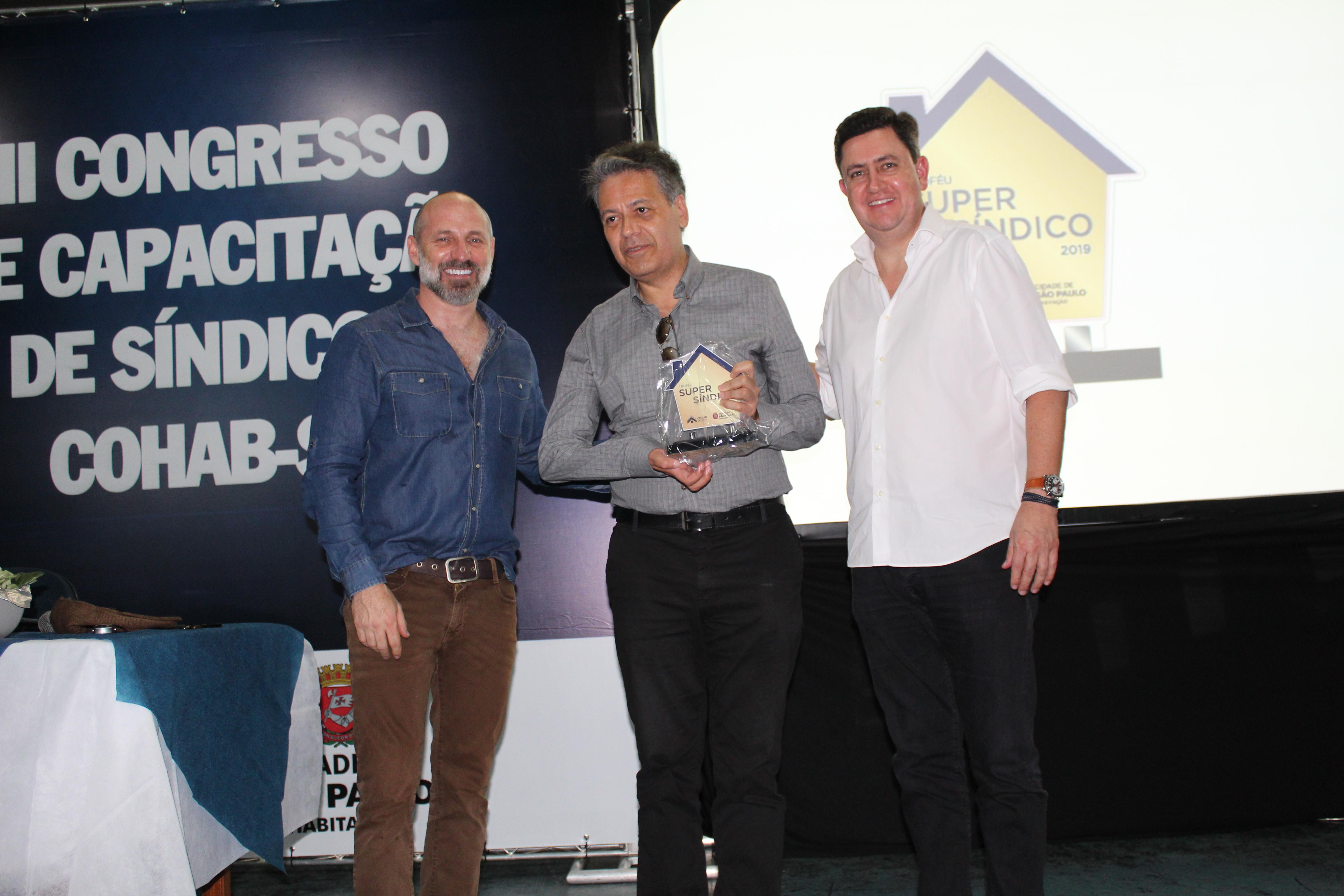 Na foto, da esquerda pra direta está Marcio Rachkorsky, no meio com o troféu o sindico João José Flores Alvarenga e ao lado dele está o presidente da Cohab Alex Peixe.